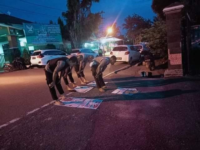 Polisi salat beralaskan koran